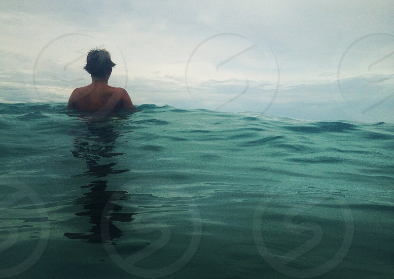 man swimming in green body of water photo