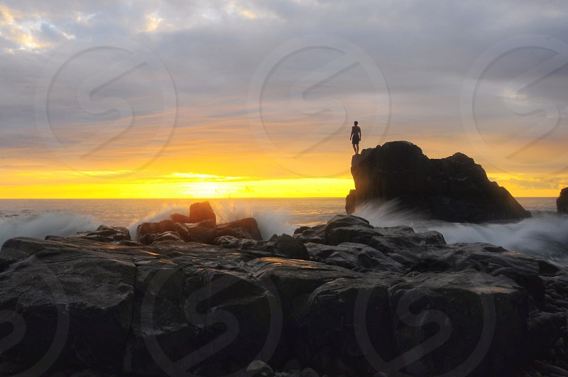 silhouette photo of man standing on cliff rock beside ocean under white cloudy sky photo
