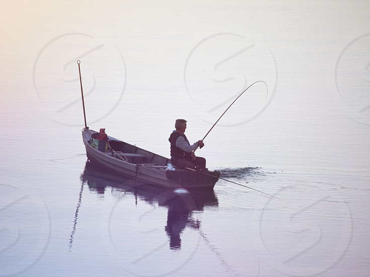 Fisherman Sitting in Flat Boat Pulling his Catch photo