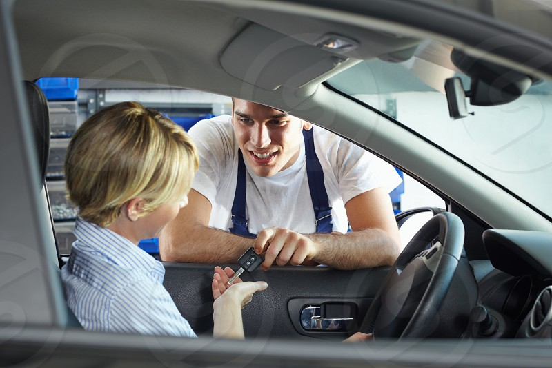 mechanic; man; woman; giving; car; key; client; people; male; female; Caucasian; young; adult; young woman; young man; mid adult; 30s; 20s; head and shoulders; blond; sitting; smiling; happy; happiness; overalls; leaning; holding; taking; keys; car keys; owner; driver; indoors; vehicle interior; inside; garage; repair station; mechanic shop; transportation; transport; vehicle; auto; automobile; broken car; repair; car repair; occupation; fixed; service; service industry photo
