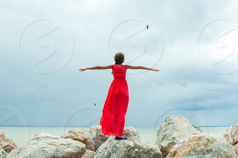 girl in red dress standing on the rocks his arms outstretched like wings of a bird in flight against the sea photo
