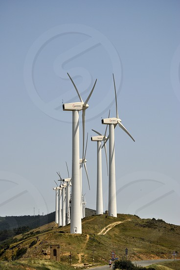 white wind turbines on hilltop during daytime photo