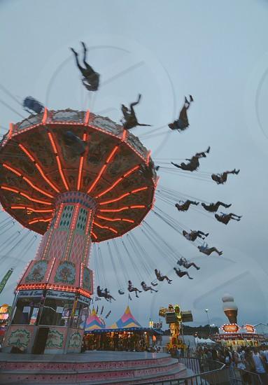 people riding yoyo ride under blue sky during daytime photo