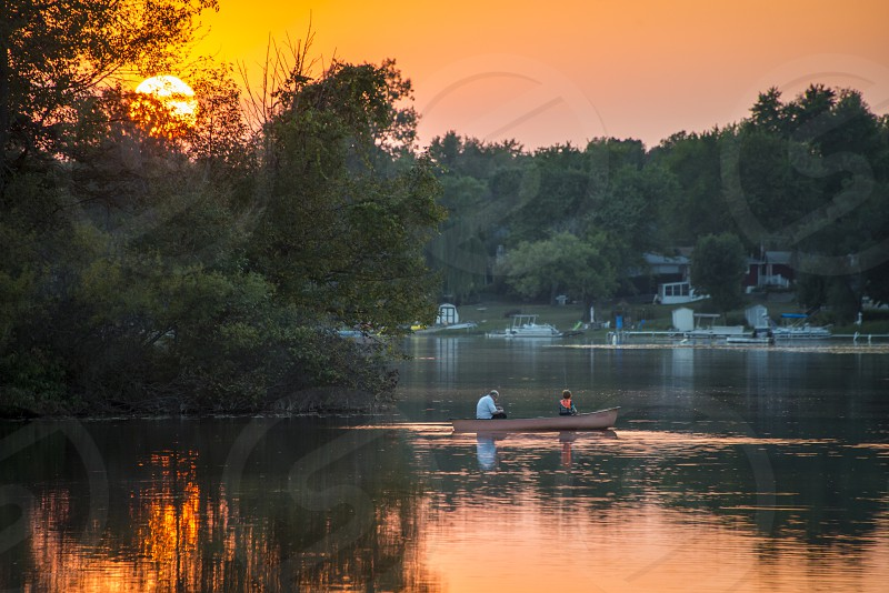 Grandfather and grandson fishing in a canoe on the lake at sunset photo