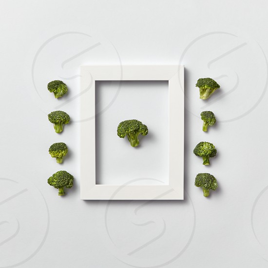 Creative organic composition with freshly picked green broccoli in a frame and out of it on a light gray background place for text. Flat lay. Vegan concept. photo