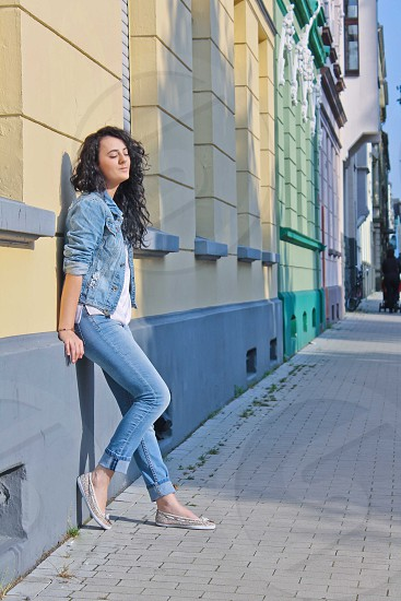brunette curly haired woman in blue denim jacket white blouse and blue denim jeans with beige boating shoes leaning against yellow and blue painted building smiling photo