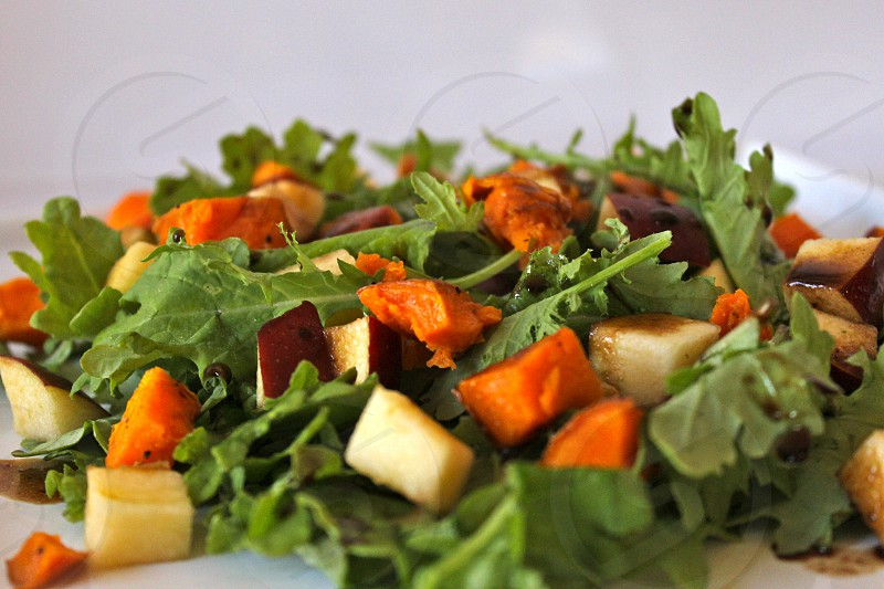 Close-up of an arugula apple and sweet potato salad. photo