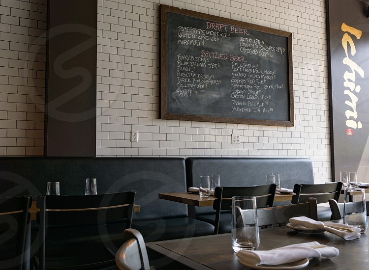 brown and green chalkboard hanging on wall near black leather sofa and table photo