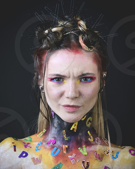 Emotional portrait of a young girl with creative makeup and colorful letters on her shoulders photo