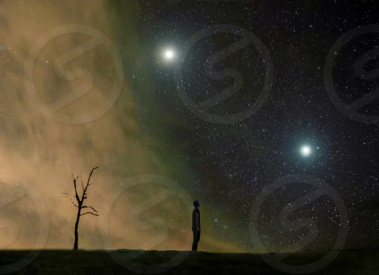 man standing under a starry night sky with light clouds and two ultra bright stars photo