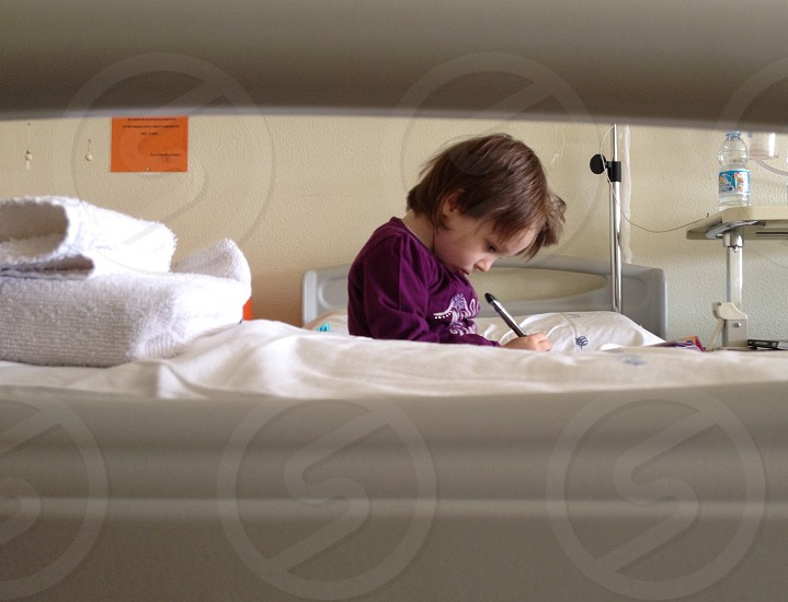 girl in purple sweater holding a ballpoint pen sitting on hospital bed photo