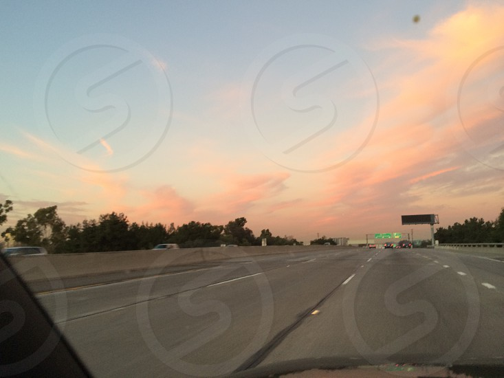 gray roadway under blue and cloudy sky at sunset photo