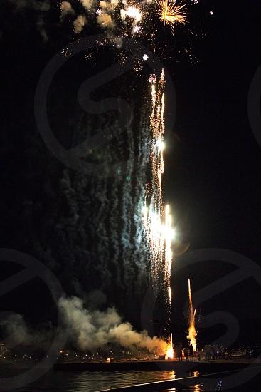 Firework rockets white on black over lake photo