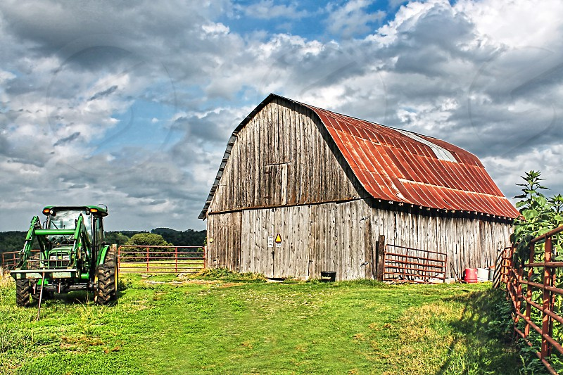 Green tractor is parked next to a weathered wooden barn photo