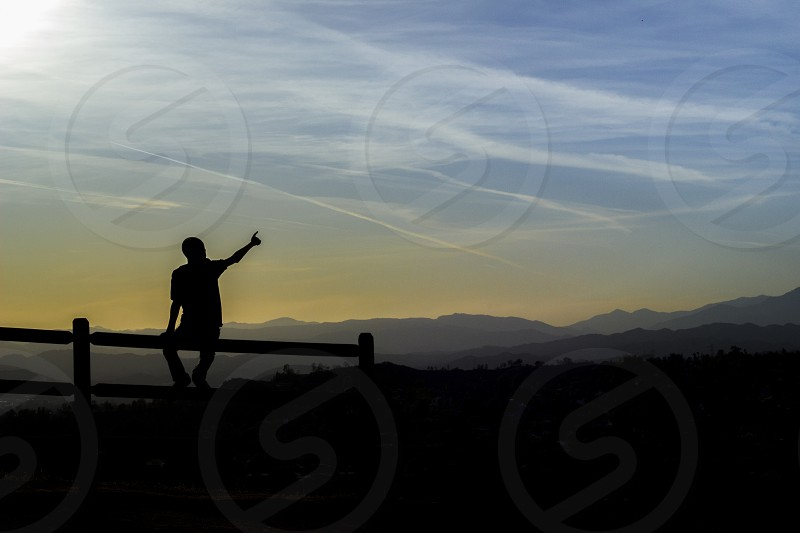 Pointing up at sky. Blue and yellow landscape background. Kid pointing up at sky while sitting on the fence.  photo