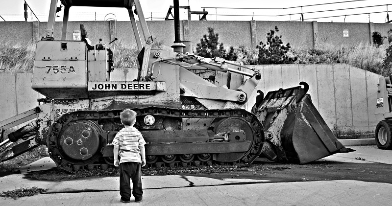 boy standing beside bulldozer in black and white photo