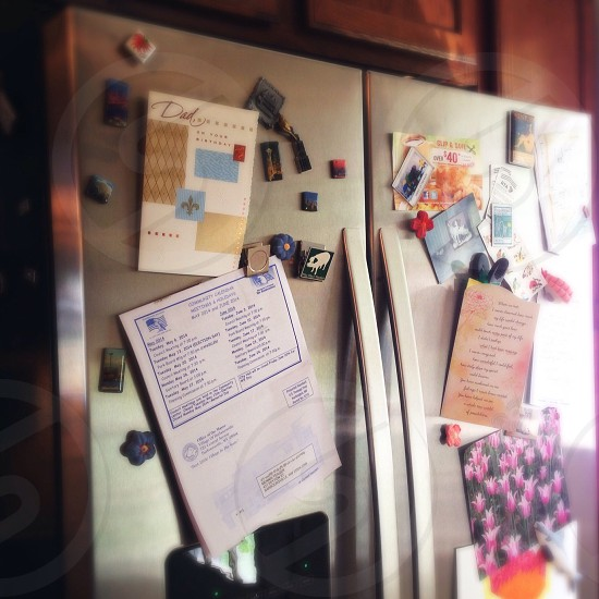 white paper with prints on stainless steel two door refrigerator photo