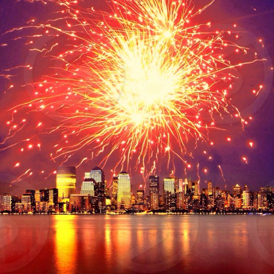 red yellow fireworks above ocean and skyscraper cityscape photo