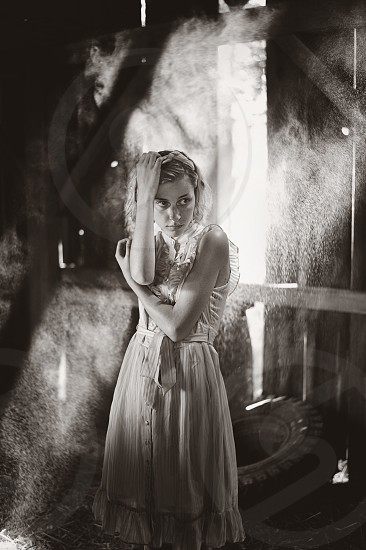 woman in white dress in a room standing grayscale photography photo