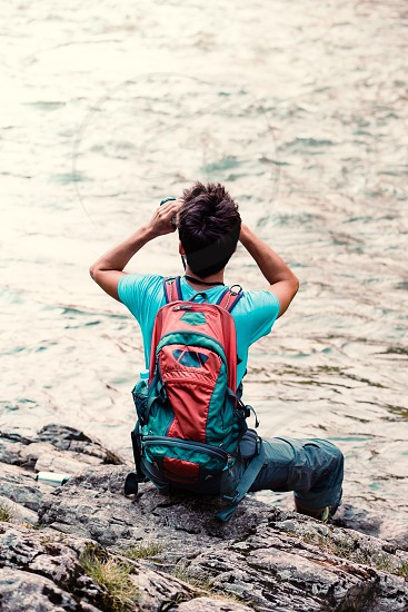 Young tourist with backpack looks through a binoculars sits on a rock over a river. Boy spends a vacation on wandering with backpack he is wearing sports summer clothes photo