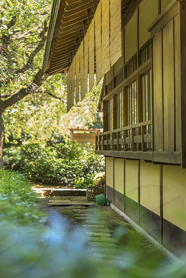 Shaded tea house lined with a circular stone path with reed canopies at its windows in Shinjuku Gyoen Park in Tokyo in Japan.  photo