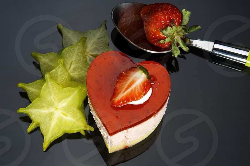 heart shaped strawberry cake with carambola or star fruit decoration over black background photo