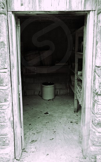 Root cellar door open with abandoned butter churn photo