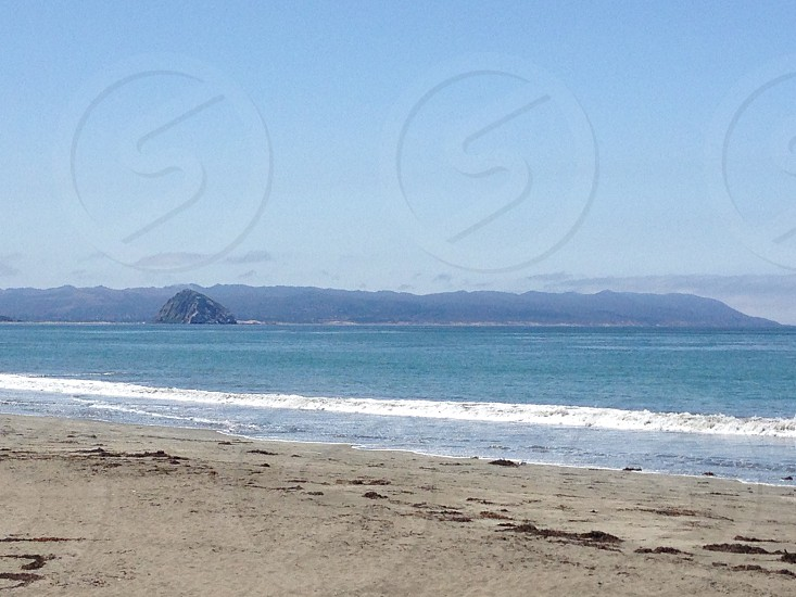 landscape photography of beach wave with mountain as background photo