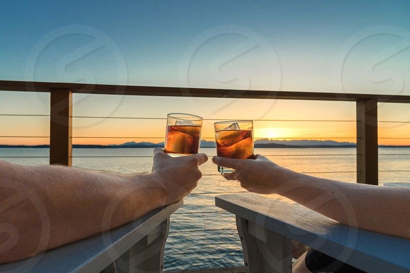 Romantic evening couple holding drinks on seaside deck at sunset photo