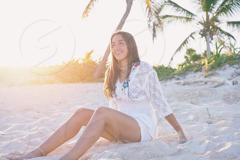 Latin beautiful girl sunset in Caribbean beach sand sitting relaxed photo