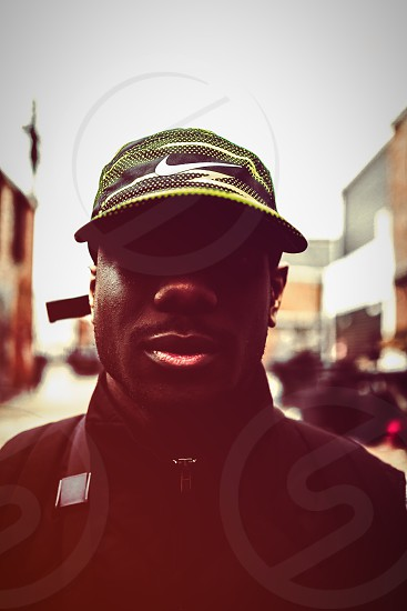 selective focus and close up photography of a man wearing a nike black white and green baseball cap and black zip up jacket photo