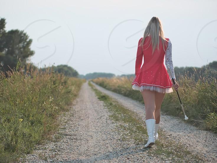 Blonde Teen Majorette Girl Twirling Baton Outdoors in Red Dress photo