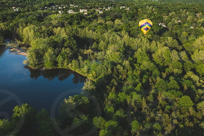 yellow hot air balloon on flight over woods by the lake photo