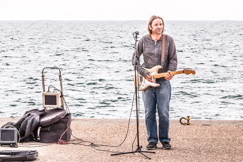 Young Man Electric Guitar Music Guitarist Player With His Audio Equipment Performing In The Street In The Front Of The Sea photo