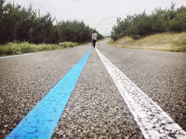 woman walking between blue and white road line photo