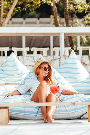Young woman drinking cocktail in a beach bar photo