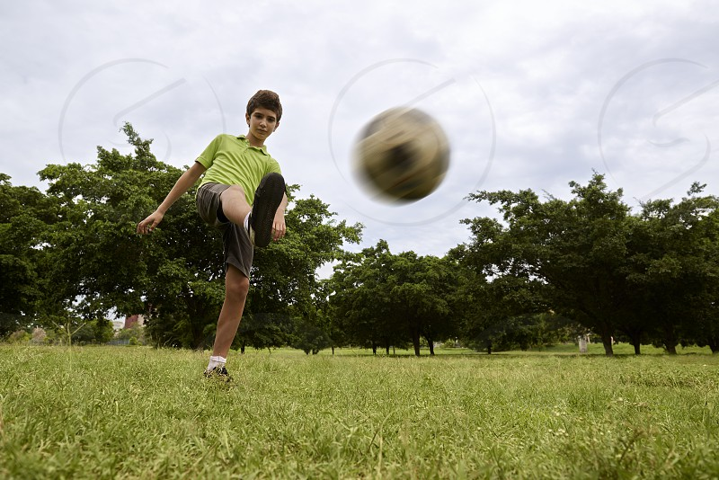 playing; soccer; football; child; children; boy; ball; 8-9; activity; blurred; caucasian; childhood; competition; concentrated; concentration; copy; copy space; copyspace; enjoy; feet; foot; fun; game; grass; green; happy; kick; kicking; kids; hit; hitting; leg; legs; leisure; lifestyle; male; match; motion; outdoor; park; people; person; player; pupil; recreation; sky; space; sport; young; youth photo