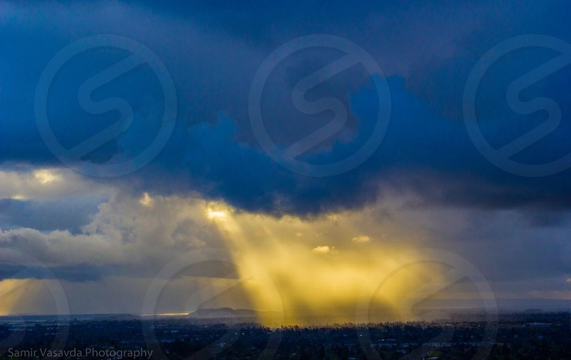 sunlight portion through the thick dark clouds photo