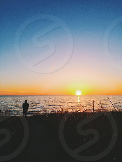 man standing looking at sea silhouette photo