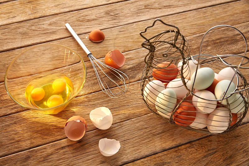 Eggs in vintage hen shape basket and shaker on wood with blue easter white and brown photo
