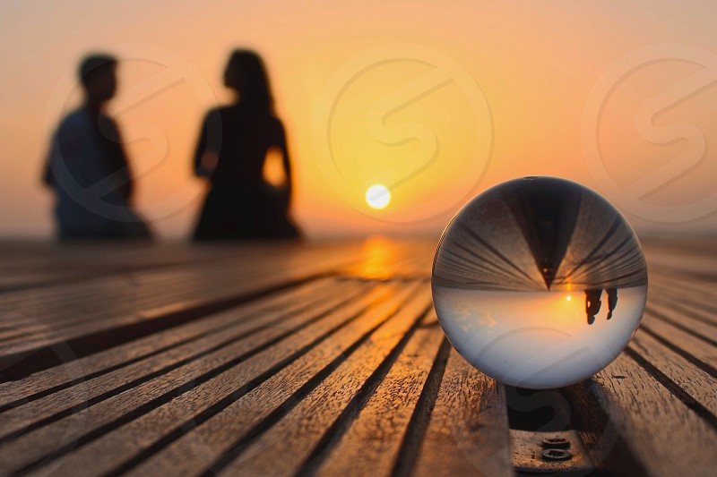 silhouette of 2 person seated on wooden dock across crystal round ball during orange sunset photo