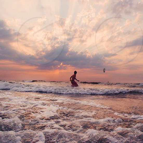 boy playing on sea shore under clear skies photo