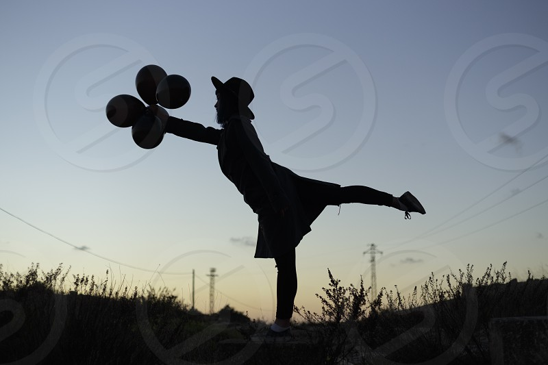 silhouette of person in hat holding balloon on grass fields photo