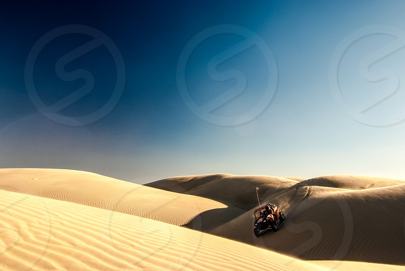 An off road vehicle drives over several large and rolling sand dunes. photo
