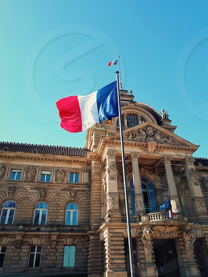 Wind blowing France flag on the mast against blue sky background in front of Palais du Rhin Place de la Republique Strasbourg Alsace. photo