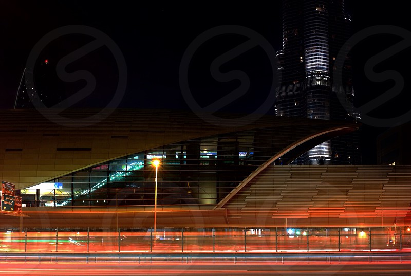 timelapse photography of lighted post lamp between concrete road at night time photo