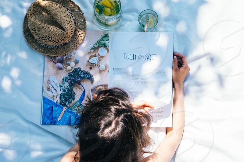 Woman reading magazine on the grass photo