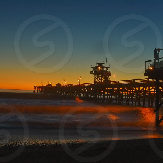 wooden dock by seashore with lights turned on during dawn photo