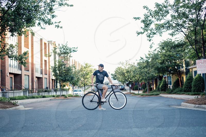 man in black t shirt riding on black road bike near trees during daytime photo