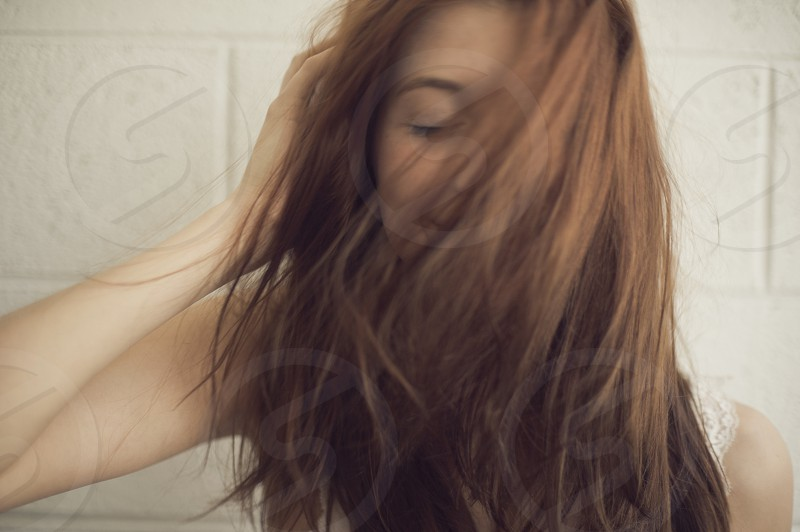 Beautiful red head woman wearing white with hair flipping in front of face photo